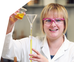 Helen Murray wearing safety goggles and smiling at the camera as she pours a yellow liquid into a funnel